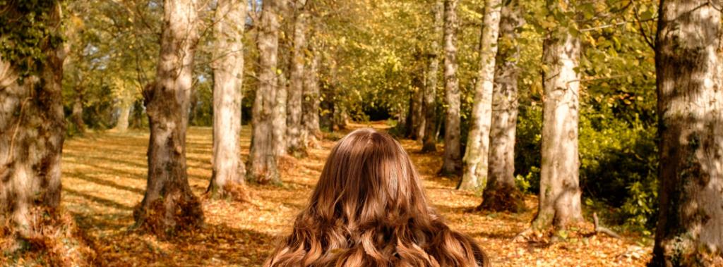 Höst i skogen med rödhårig kvinna